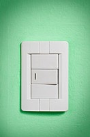 White light switch on green wall