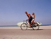 Young Couple Riding Bicycle on Beach