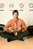 Businessman Meditating in Conference Room