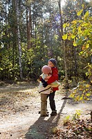 Two children embrace each other in autumn forest