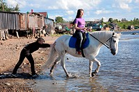 Female lead a horse to swim
