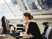 Businesswoman Studying Information on Computer Screens