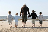 Grandfather with Grandchildren Walking on Beach