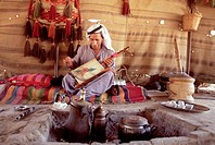 A Bedouin man plays a rabab in his tent