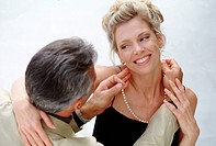 Man putting pearls on girlfriend