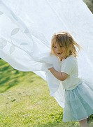 Little Girl Playing with Laundry Hanging on Clothesline