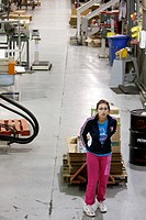 A woman at a plastics molding injection plant pulls a pallet jack