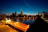 The Frankfurt am Main skyline and boat restaurants moored on the Main river, seen from Alte brücke bridge at sunset, Germany, Europe