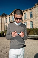 Paris, France, Young Chinese Tourist Visiting in Garden of Rodin Museum, Sending Text with Smart Phone, Iphone