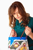 Woman looking into shopping bag with Christmas theme