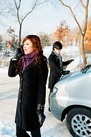 Businesswoman talking on the phone, businessman looking at map in the background