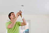 Electrician fitting energy saving lightbulb fitting