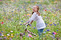 Smiling girl riding bicycle in wildflower meadow