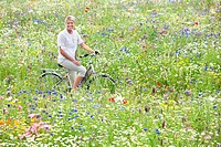Portrait of smiling woman riding bicycle in wildflower field