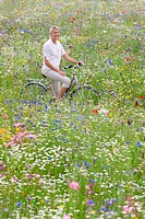 Smiling woman riding bicycle in wildflower field