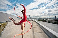 Dancer with ribbon on urban rooftop