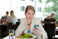 Businesswoman using cell phone at lunch
