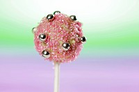 A cake pop, chilled and decorated with light chocolate and sugar strands