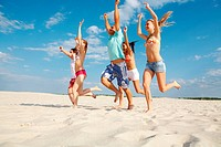 Photo of happy friends running down sandy beach with raised arms