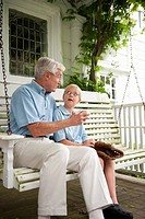 Grandfather and grandson 10_11 sitting on porch swing