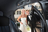 Newly wed couple near limousine