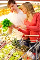 Portrait of happy couple choosing greenery in supermarket