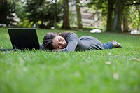 Young woman lying on grass using laptop