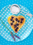 A heart_shaped blueberry pancakes with icing sugar and lavender flowers