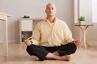 Mature businessman meditating in office