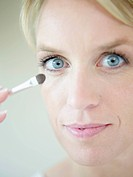 Mature woman doing make up with brush