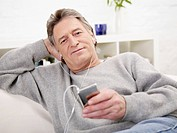 Germany, Hamburg, Senior man listening MP3 player (thumbnail)