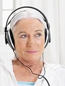 Germany, Hamburg, Senior woman listening music