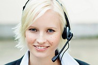 Germany, Bavaria, Munich, Young woman with headset, smiling, portrait