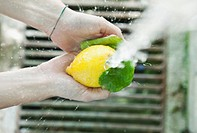 Italy, Tuscany, Magliano, Close up of woman washing lemon under water