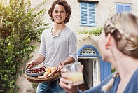 Italy, Tuscany, Magliano, Young man holding basket with apples and cherries with woman in foreground, smiling