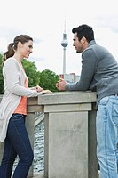 Germany, Berlin, Couple standing on bridge and talking (thumbnail)