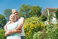 Germany, Bavaria, Man and woman embracing each other in garden, smiling