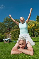 Germany, Bavaria, Woman sitting on top of man while exercising in garden