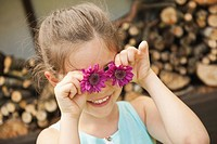 Germany, Bavaria, Girl holding flowers as eyes, smiling