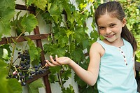 Germany, Bavaria, Girl standing by grape vine, smiling, portrait