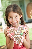 Germany, Bavaria, Girl with gingerbread heart, smiling, portrait