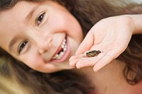 Germany, Bavaria, Human hand with little frog, girl smiling in background