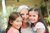 Germany, Bavaria, Granddaughters and grandmother smiling, portrait