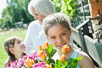 Germany, Bavaria, Granddaughters and grandmother in garden, smiling