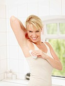 Mature woman putting deodorant on underarms, smiling, portrait