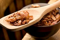Bacon bits on a wooden bowl and on a spoon