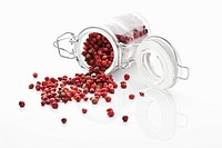 Dry red pepper in glass jar spilling on white background