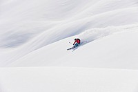 Austria, Zurs, Lech, Young woman doing alpine skiing on Arlberg mountain