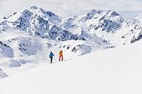 Austria, Stuben, Young couple doing telemark skiing on arlberg mountain