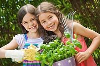 Germany, Bavaria, Sisters doing gardening in garden, smiling, portrait